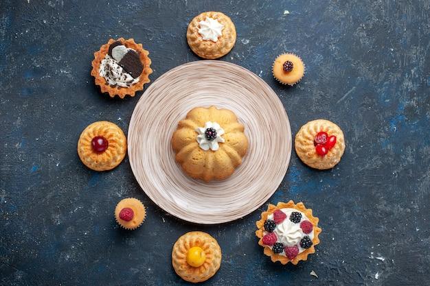 Вид сверху маленькие вкусные торты, разные сформированные на темном бисквитном пироге, сладкая фруктовая выпечка