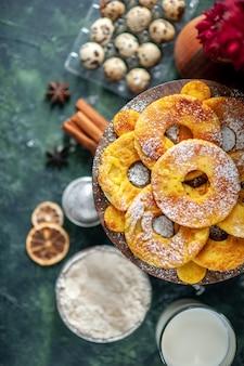 Вид сверху маленькие вкусные пирожные в форме кольца ананаса с молоком на темном фоне, горячее пирожное, выпечка, пирог, печенье, торт, фруктовая выпечка