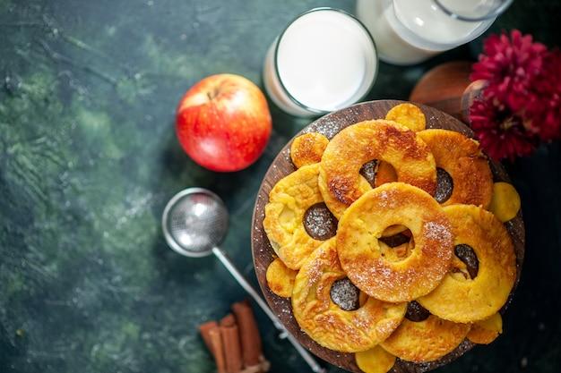 Вид сверху маленькие вкусные пирожные в форме кольца ананаса с молоком на темном фоне, горячее пирожное, выпечка, пирог, цветное печенье, печенье, торт, фрукты