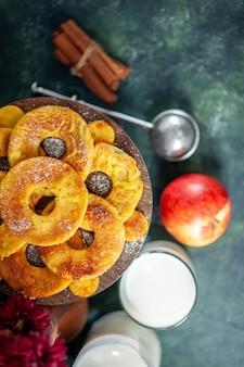 Вид сверху маленькие вкусные пирожные в форме кольца ананаса с молоком на темном фоне, горячее пирожное, выпечка, пирог, цветное печенье, торт, фруктовый бисквит.