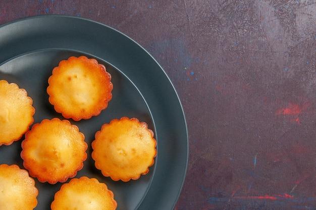 Вид сверху маленькие вкусные пирожные внутри тарелки на темной поверхности пирог бисквитный торт сладкий чай сахарное печенье