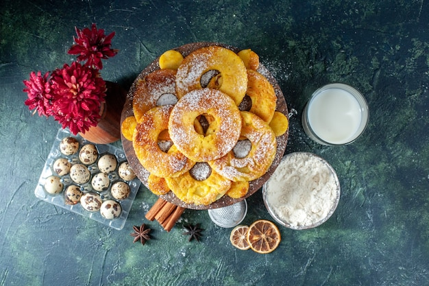 Vista dall'alto piccole deliziose torte a forma di anello di ananas con latte sullo sfondo scuro hotcake torta al forno torta biscotto pasticceria alla frutta