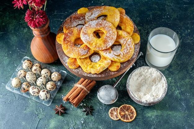 Vista dall'alto piccole deliziose torte a forma di anello di ananas con latte su sfondo scuro hotcake torta al forno biscotto torta di frutta pasticceria