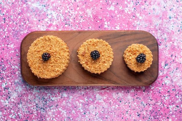 Vista dall'alto di piccole deliziose torte rotonde formate sulla superficie rosa