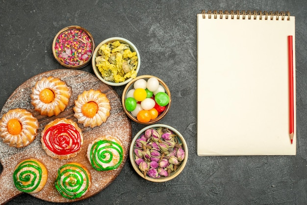 Top view of little delicious cakes with candies and flowers on dark
