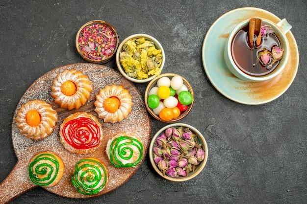 Vista dall'alto di piccole deliziose torte con tè di caramelle e fiori su fondo nero