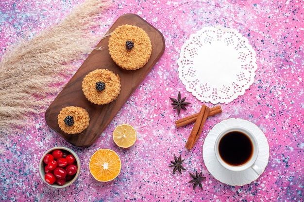 Top view of little delicious cakes with cinnamon and cup of tea on light-pink surface