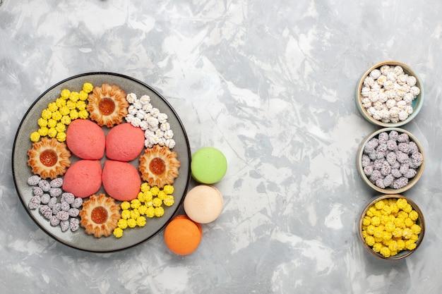 Vista dall'alto piccole deliziose torte con biscotti e caramelle sulla scrivania bianca caramella dolce biscotto torta torta zucchero torta biscotto