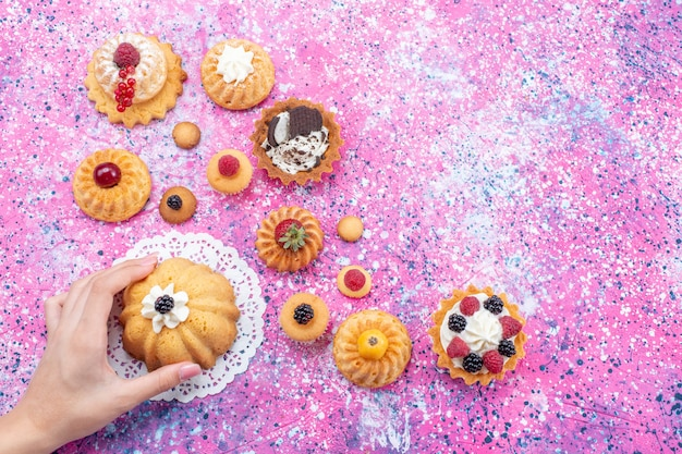 Vista dall'alto piccole deliziose torte con crema insieme a diversi frutti di bosco sullo sfondo luminoso torta biscotto bacca cuocere