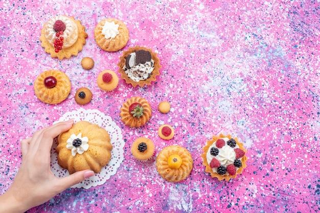 トップビュー明るい背景のケーキビスケットベリーベイクのさまざまなベリーと一緒にクリームとクリームと少しおいしいケーキ
