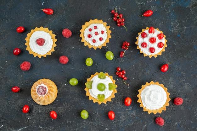 Вид сверху маленькие вкусные пирожные со сливками и свежими фруктами на темных фруктах стола