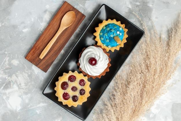 トップビューライトデスクケーキのクリームとフルーツの小さなおいしいケーキ甘いクリーム焼きフルーツ