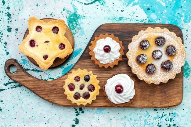 トップビューライトテーブルケーキビスケットスウィートティークリームにクリームとフルーツの小さなおいしいケーキ