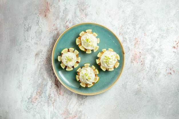 흰색 표면 케이크 비스킷 쿠키 달콤한 차 설탕에 크림과 레몬 조각과 상위 뷰 약간 맛있는 케이크