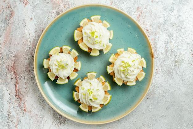 上面図白い表面にクリームとレモンのスライスが付いた小さなおいしいケーキビスケットクッキースウィートティーシュガー