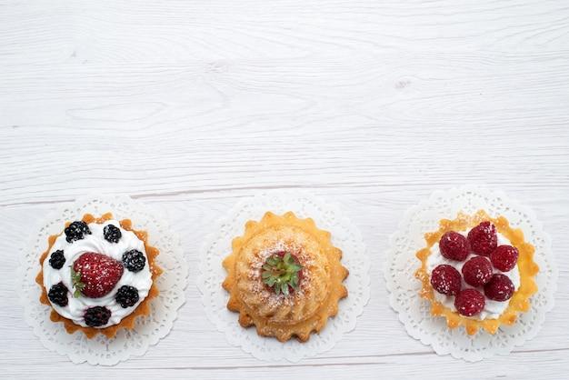 Vista dall'alto piccole deliziose torte con crema e frutti di bosco sullo sfondo chiaro torta biscotto frutti di bosco zucchero dolce