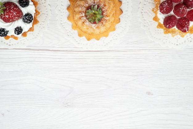 Vista dall'alto piccole deliziose torte con panna e frutti di bosco sullo zucchero dolce scrivania luce torta biscotto frutti di bosco