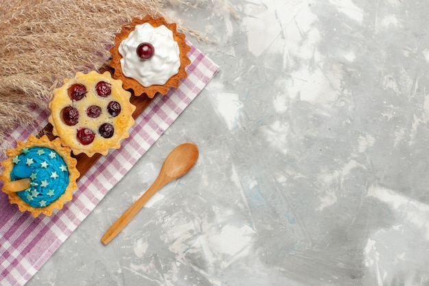 Top view little delicious cakes with cream and fruits on the light background cake sweet cream bake fruit
