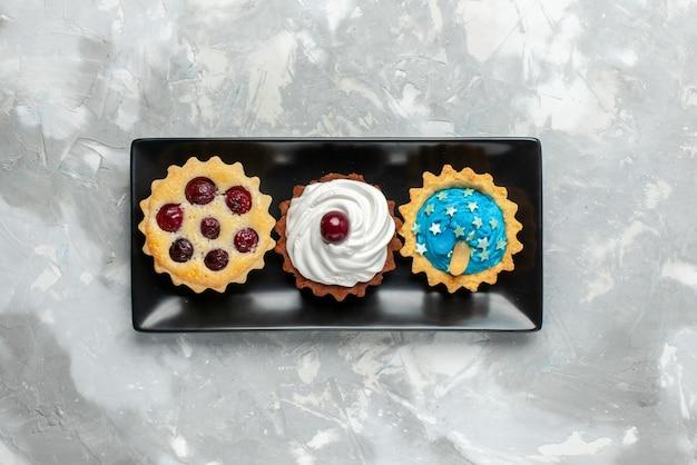 Vista dall'alto piccole deliziose torte con crema e frutta sulla torta da tavolo leggera con crema dolce cuocere la frutta
