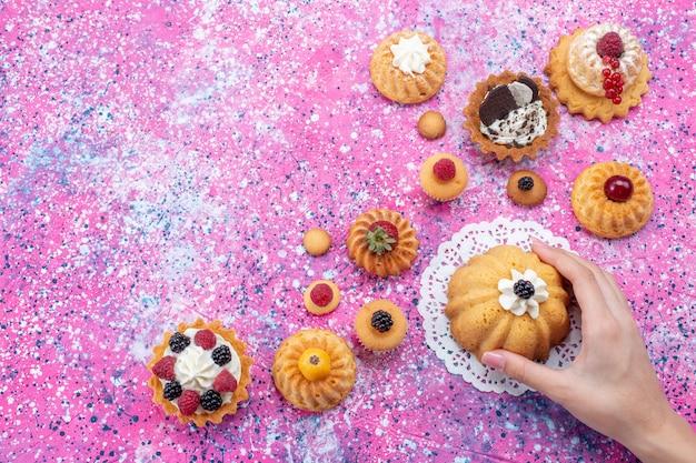 明るい机の上のさまざまなベリーと一緒に女性がクリームを手に入れている小さなおいしいケーキの上面図ケーキビスケットベリースイートベイク