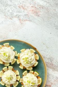 Vista dall'alto piccole deliziose torte con crema e fette di limone su una superficie bianca chiara torta biscotto biscotto dolce tè zucchero