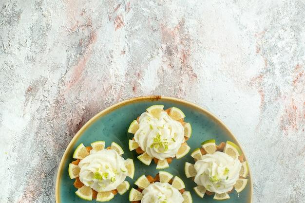 Vista dall'alto piccole deliziose torte con crema e fette di limone su superficie bianca torta biscotti biscotti dolce tè zucchero