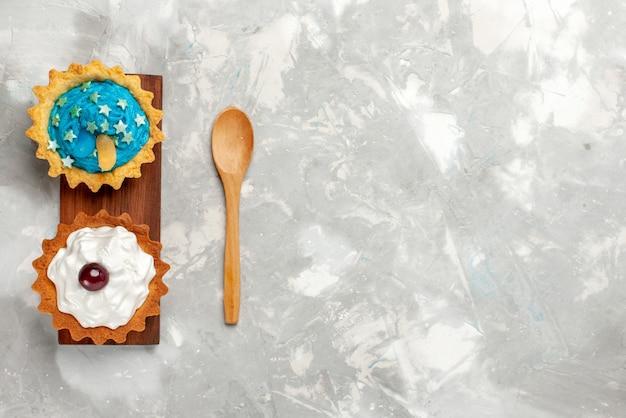 トップビュー明るい背景のケーキビスケットスウィートティークリームにクリームと少しおいしいケーキ