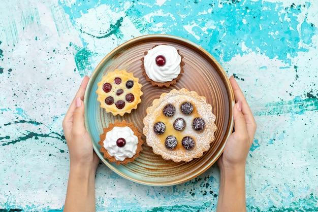 Вид сверху маленькие вкусные пирожные со сливками на голубом столе торт бисквит сладкий чай крем