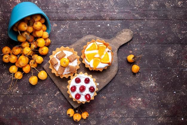 Вид сверху маленькие вкусные пирожные с нарезанными сливками фруктами и свежей желтой вишней на коричневом деревянном фоне, свежий фруктовый торт, бисквитный сладкий