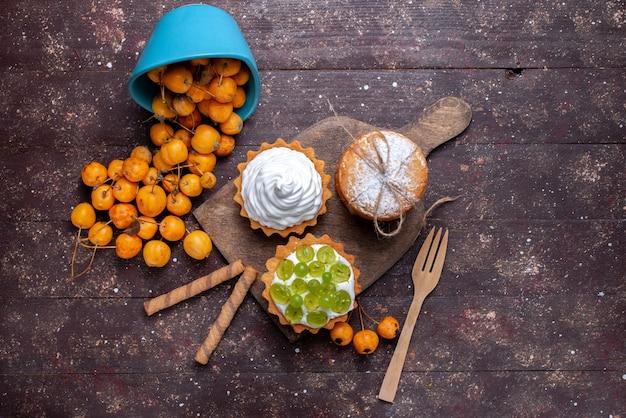 Вид сверху маленькие вкусные пирожные с кремом, ломтиками виноградного печенья и свежей желтой вишней на коричневом столе, свежий фруктовый торт, бисквит, черешня