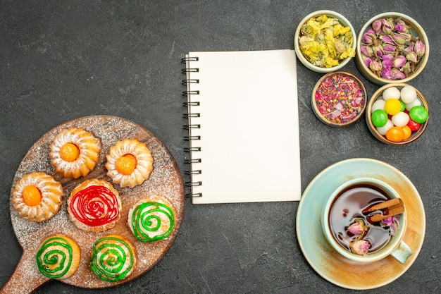 Vista dall'alto di piccole deliziose torte con una tazza di caramelle da tè e fiori su grigio nero