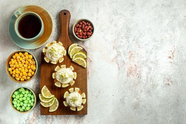 Vista dall'alto piccole deliziose torte con una tazza di tè e caramelle sulla superficie bianca torta biscotto biscotto crema di tè dolce