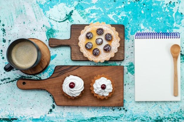 Вид сверху маленькие вкусные пирожные с фруктами, молоком и блокнотом на голубом фоне торт сладкий сахарный крем цветное фото