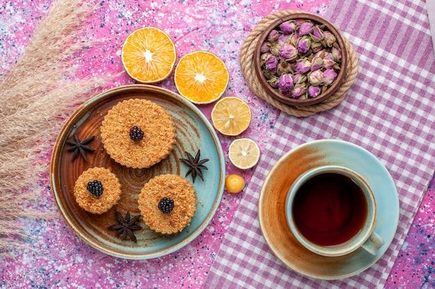 Vista dall'alto di piccole deliziose torte con fette d'arancia e tè sulla superficie rosa
