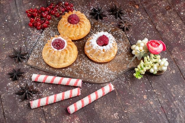 上面図ラズベリーとクランベリーの小さなおいしいケーキと木製の机の上のスティックキャンディーケーキ甘いフルーツ焼きビスケットベリー