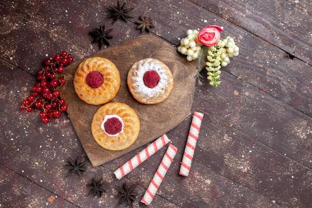 上面図ラズベリーと新鮮なクランベリーと木の机の上のスティックキャンディーと小さなおいしいケーキケーキ甘い砂糖の果実の写真