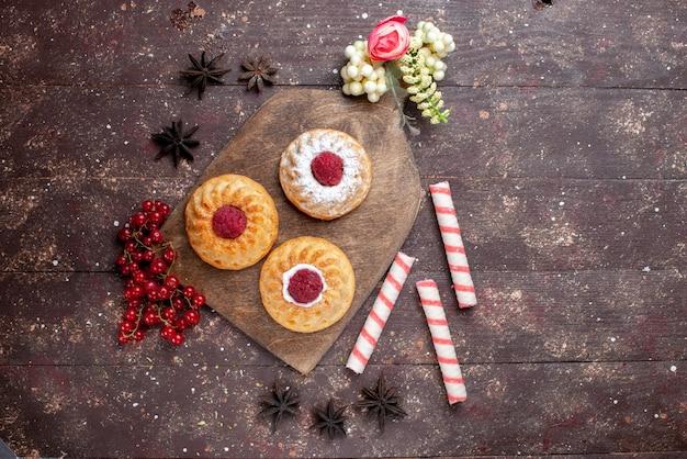 Vista dall'alto piccole deliziose torte con lamponi e mirtilli rossi freschi insieme a caramelle in stick sulla torta da scrivania in legno marrone dolce zucchero frutta foto