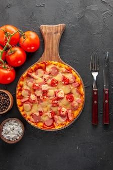 暗いテーブルの上にトマトとカトラリーが入った小さなおいしいピザの上面図