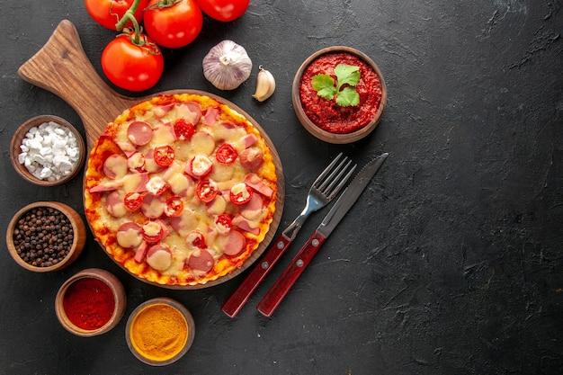 暗いテーブルにトマトと調味料を入れたトップビューの小さなおいしいピザ