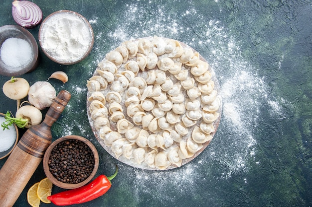 暗い背景に小麦粉と野菜が入った小さな餃子の上面図肉生地食品皿色野菜ミール
