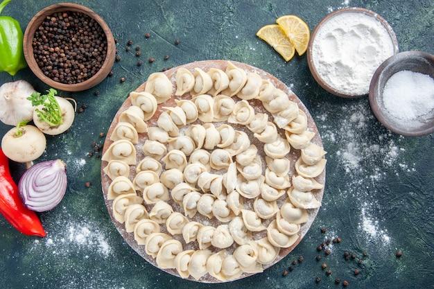 上面図濃い灰色の背景に小麦粉と小さな餃子生地の色食品食品皿肉カロリー食事