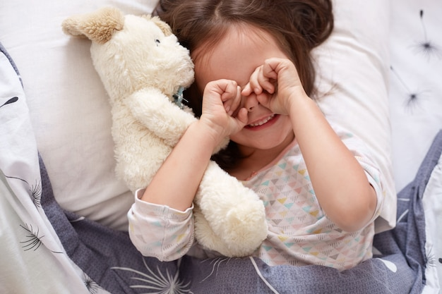 Top view of little girl cry in bed with teddy bear, toddler laiyng on linens with dandelion, charming kid rubbing her eyes after wakes up