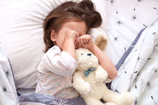 Top view of little girl lying in bed with teddy bear, being in bad mood, does not want to srtand up and go to kinder garten, toddler on pillow rubbing her eyes