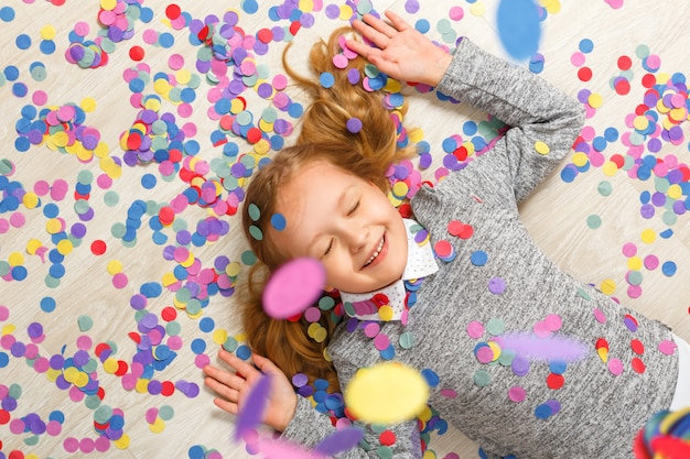 Top view of a little girl lying on the floor under falling confetti.