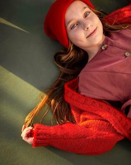 Вид сверху маленькая девочка, лежащая на баскетбольном поле