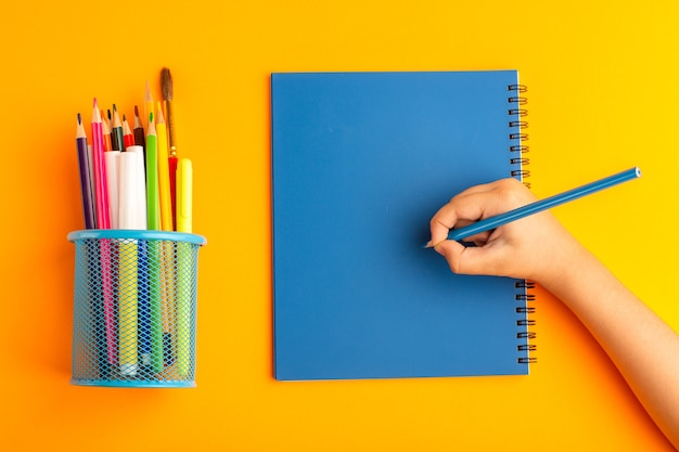 Top view little kid drawing and writing something on copybook on the orange surface