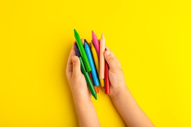 Вид сверху маленький ребенок держит красочные карандаши на желтой поверхности