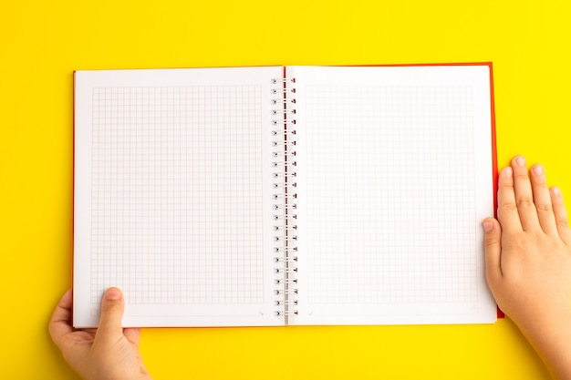 노란색 책상에 카피 북을 들고 상위 뷰 작은 아이
