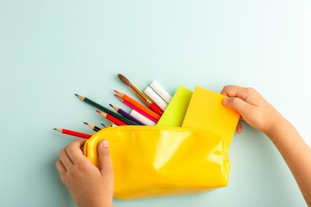 Vista dall'alto ragazzino che tiene la scatola della penna gialla piena di matite colorate sulla superficie blu ghiaccio