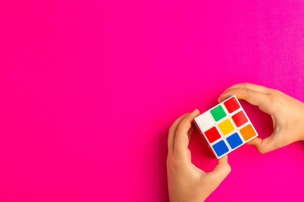 Вид сверху маленький ребенок играет с кубиком рубика на фиолетовом столе